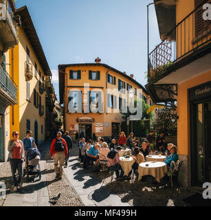 Bellagio, Italy - October 7, 2017: Tourists on narrow street with colorful houses in small town of Bellagio, Italy during sunny day. Como Lake - Stock Photo