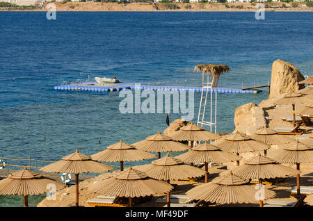 On the seashore you can see a pantone with a boat and sun umbrellas - Stock Photo