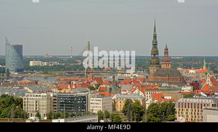 Aerial view on Riga, showing the Saint Peter`s church tower, modern suspension bridge and skyscraper. - Stock Photo