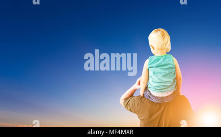 funny little boy sit on father's shoulder with sunset background - Stock Photo