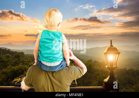 small boy sit on father's shoulder and looking at sunset view on mountain - Stock Photo