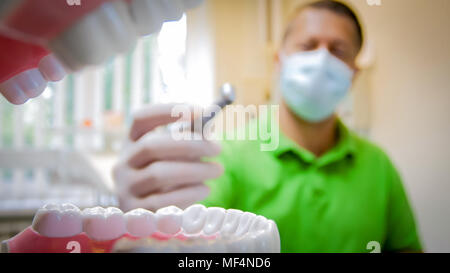 View from inside of mouth of doctor holding dental drill - Stock Photo