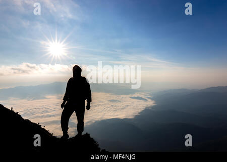 silhouette traveler stand alone on cliff with mist and sunshine with blue sky in Thailand - Stock Photo