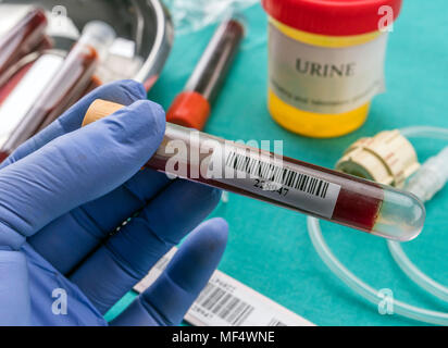 Doctor holds blood sample at a hospital table, conceptual image - Stock Photo