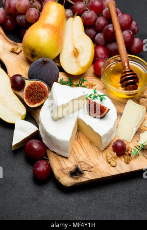 Slice of French brie or camembert cheese and pear on wooden board - Stock Photo