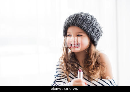 A small happy girl in striped T-shirt at home applying a lipstick. - Stock Photo