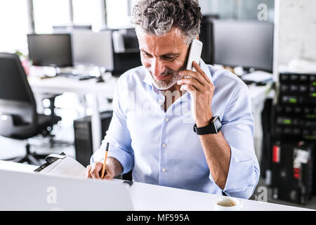 Smiling mature businessman sitting at desk in office talking on smartphone - Stock Photo