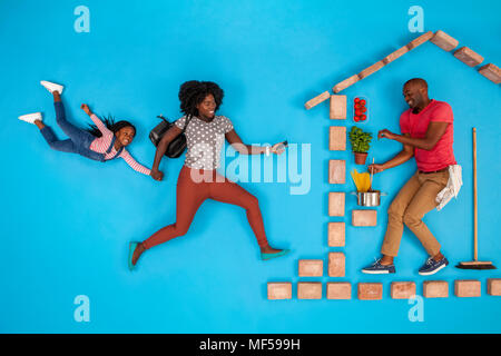 Mother and daughter coming home, father preparing food - Stock Photo