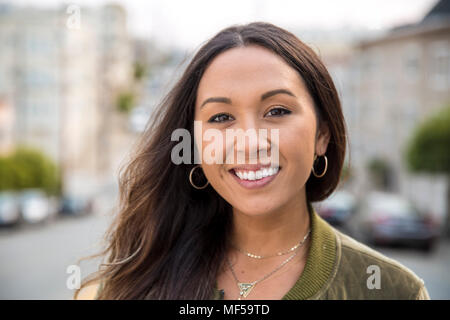 Portrait of smiling young woman on the street - Stock Photo
