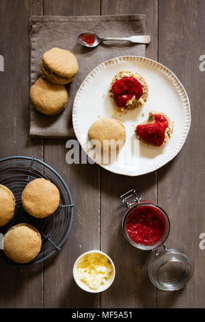 Scones made of einkorn wheat with strawberry jam and clotted cream - Stock Photo