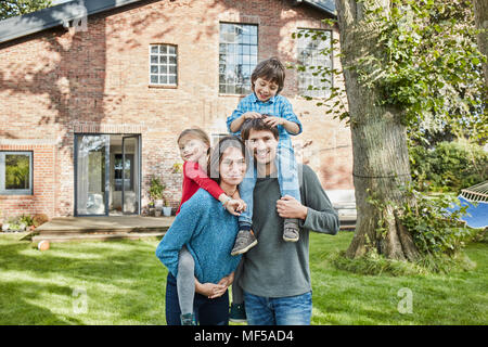 Portrait of happy family in garden of their home - Stock Photo