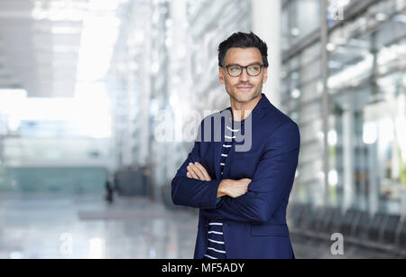Portrait of stylish businessman with stubble wearing blue suit and glasses - Stock Photo