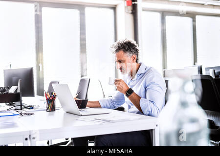 Mature businessman sitting at desk in office using laptop and drinking coffee - Stock Photo