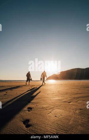 Canada, British Columbia, Vancouver Island, two men walking on beach at San Josef Bay at sunset - Stock Photo