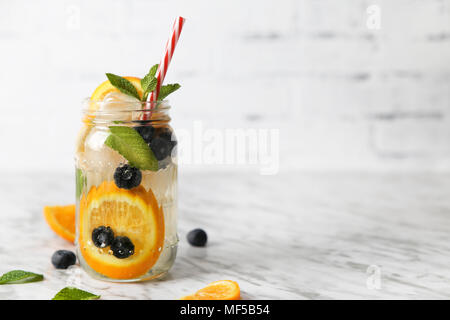 Glass of infused water with orange, blueberries and mint on ice - Stock Photo