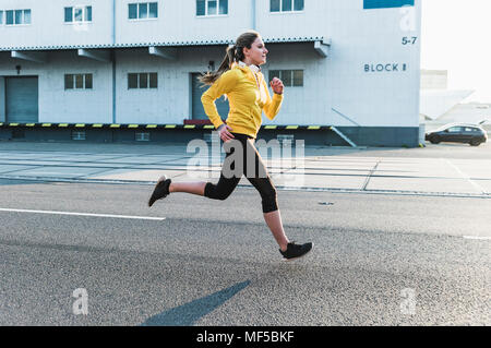 Young woman running on a street - Stock Photo