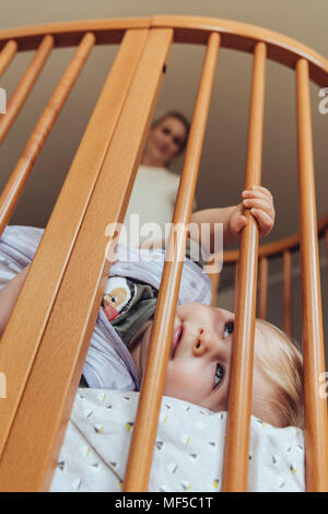 Baby lying in crib with open eyes, mother watching in background - Stock Photo