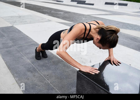 Fit woman doing push ups outdoors - Stock Photo