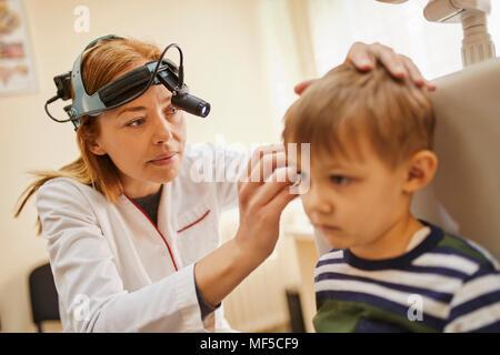 ENT physician examining ear of a boy - Stock Photo