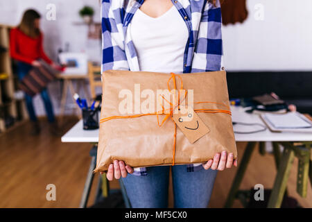 Close-up of fashion designer holding a wrapped package in studio with smiley face - Stock Photo
