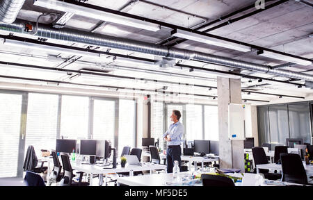 Mature businessman standing in open plan office - Stock Photo