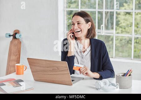 Laughing businesswoman on cell phone at desk holding card - Stock Photo