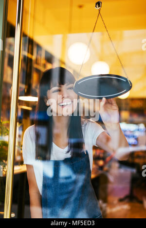 Happy woman turning sign in window of a store - Stock Photo
