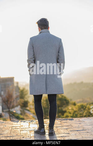 Back view of fashionable young man wearing grey coat - Stock Photo