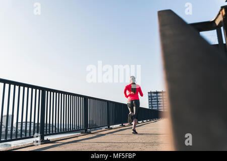 Young woman running on bridge in the city - Stock Photo