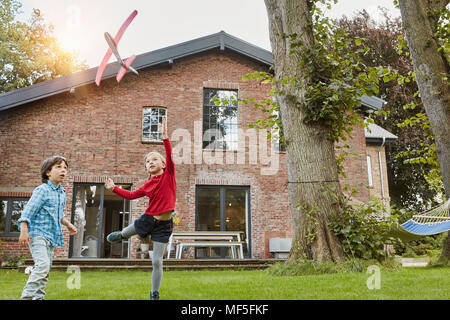 Two children playing with toy airplane in garden of their home - Stock Photo