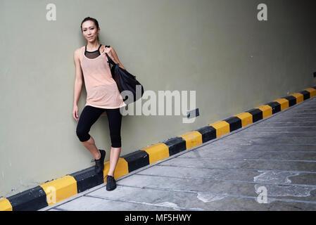 Portrait of confident fit woman holding a bag - Stock Photo