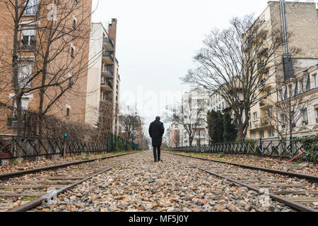 France, Paris, back view of man walking along abandoned railway tracks - Stock Photo