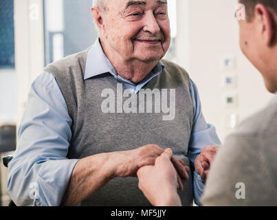 Senior man smiling at young man holding his hands - Stock Photo
