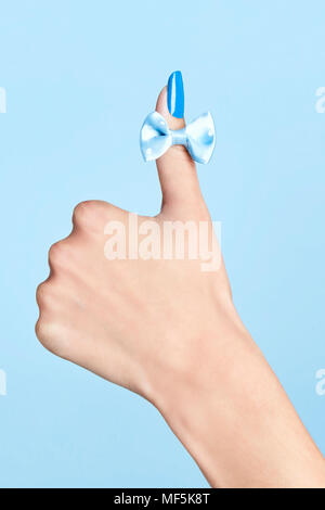 Close-up of bow tie on woman's thumb - Stock Photo