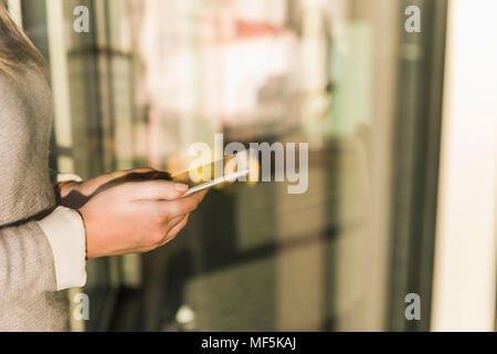 Close-up of businesswoman holding cell phone - Stock Photo