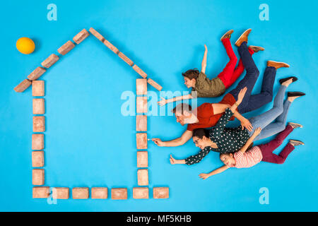 Happy family with keys coming to their new home - Stock Photo