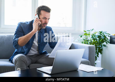Serious man with documents and laptop on sofa talking on cell phone - Stock Photo