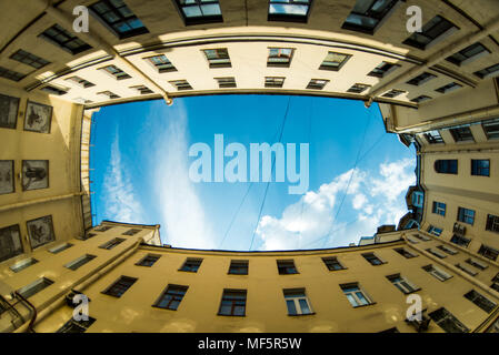Courtyard city look up with fisheye lens effect. Low angle shot of building with windows and cloudy sky background. - Stock Photo