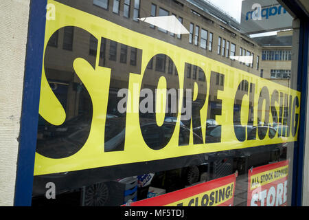 store closing sign in front shop window closing down sale England UK - Stock Photo
