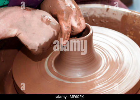potter working clay on a spinning wheel in the uk - Stock Photo
