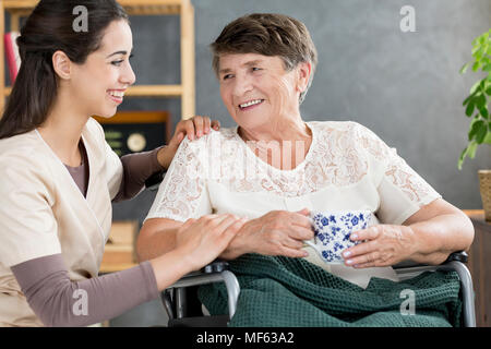 Beautiful caregiver talking to a pensioner in a wheelchair while having a tea - Stock Photo