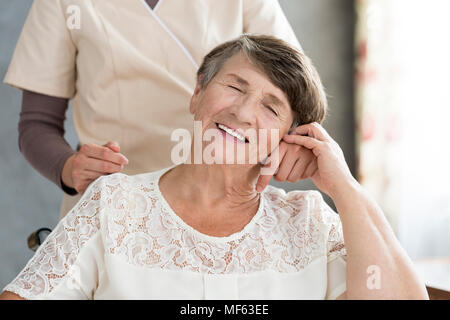 Dreaming pensioner holding the hand of her nurse in a senior home - Stock Photo