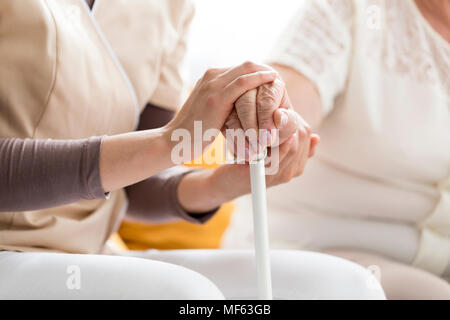Woman comforting a blind, senior lady, holding a cane - Stock Photo