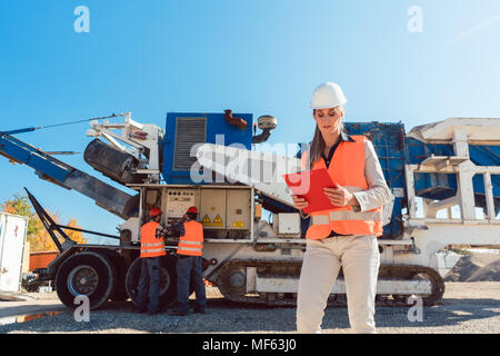Civil Engineer woman with clipboard in front of stone crusher - Stock Photo