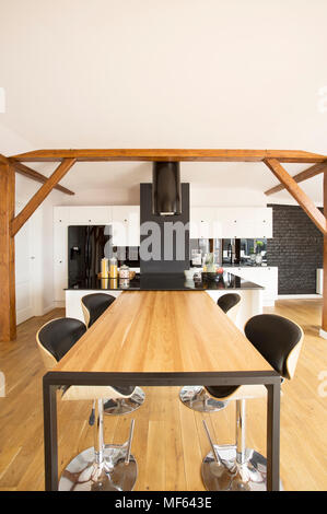 Bar stools at wooden table in spacious kitchen interior with black countertop and white cabinets - Stock Photo
