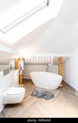 Oval bathtub and toilet in minimalist, bright, white bathroom interior - Stock Photo