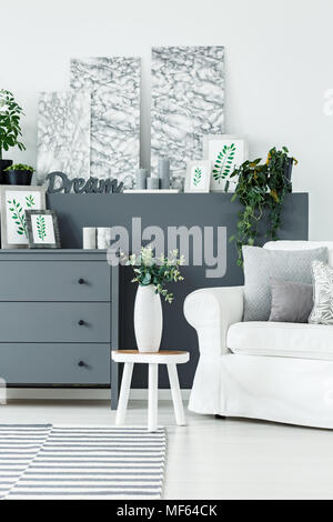 Fresh flowers in a white vase placed on a small wooden table in bright room interior with paintings, grey cupboard and candles - Stock Photo