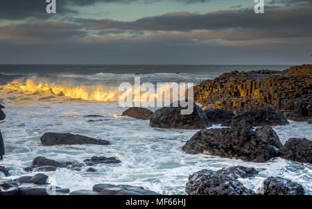 The waves crashing over the hexagonal rock formation at the Giant Causeway just before sunset, Northern Ireland, UK - Stock Photo