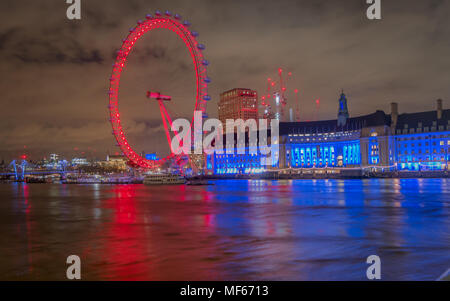 London, England, United Kingdom - June, 2016. Enjoying a lovely view of the London eye lit with colorful lights at night from the westminster bridge - Stock Photo