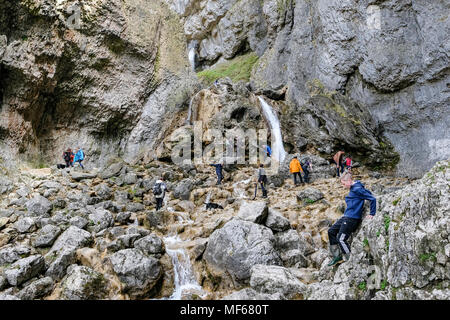 Walkers and tourists at Gordale Beck running through Goredale Scar, Malham, Malhamdale, North Yorkshire, Yorkshire Dales National Park, England, UK - Stock Photo